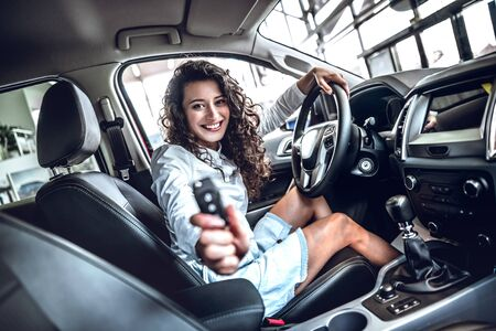 Happy smiling driver woman showing car key sitting in new auto. Side view