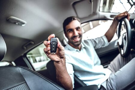Handsome man showing a car key inside his new vehicle. Side view. Focus on key
