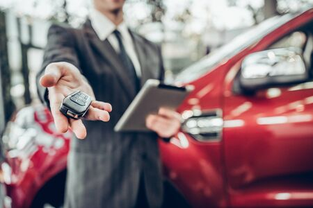 Man in suit offering a car key to the observer, with a car in the background. Close up view. Focus on key 스톡 콘텐츠