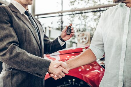 Auto business, car sale, deal, gesture and people concept - close up view of dealer giving key to new owner and shaking hands in auto show or salon
