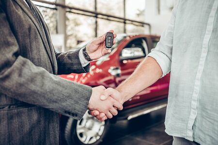 Buying a new car. Handshake and handing over the keys to the car by the salon consultant to the buyer.