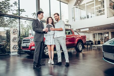 Online payment. Beautiful happy couple buying a car at car salon showroom handsome car salesman showing something on a digital tablet to his customers lifestyle communication technology online device