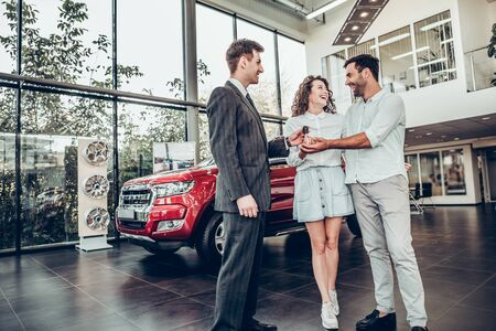 Car salesman is giving the key of the new car to the young attractive owners.