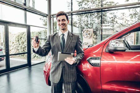 Great choise! Handsome young classic car salesman standing at the dealership holding a key.