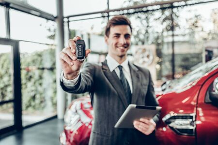 Salesman in grey suit holding car key on red car background. focus on key.