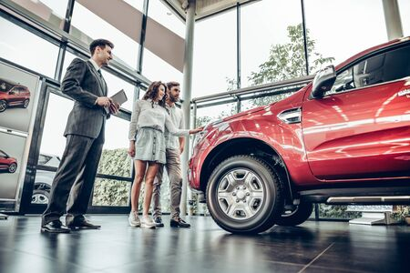 Salesman presenting special offers to clients. car salesman showing new vehicle to family customers. bottom view