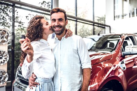 We have made the right choice. Handsome young men standing near the car at the dealership hugging and kissing his wife. Young woman holding a key