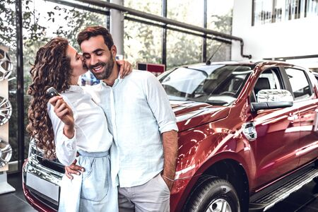 Visiting car dealership. Beautiful couple is holding a key of their new car and smiling, girl is kissing her husband in cheek