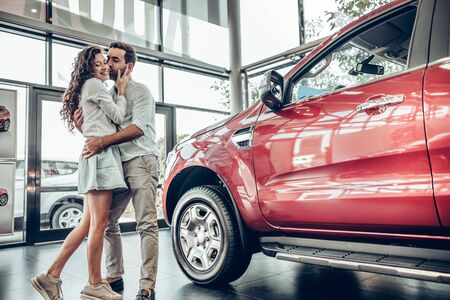 Visiting car dealership. Beautiful couple is hugging and smiling, man is kissing her wife in cheek 스톡 콘텐츠