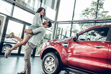 Beautiful young couple is smiling while buying a car in a motor show. Man is holding woman in his arms. Bottom view