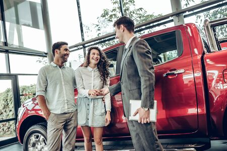 Now her dream comes true. Car salesman giving the key of the new car to the young attractive owners. Red car background