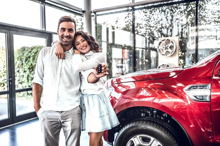 Happy young lovely couple in casual wear hugging while buying first new family car together in dealership. Woman shows car key on camera 스톡 콘텐츠