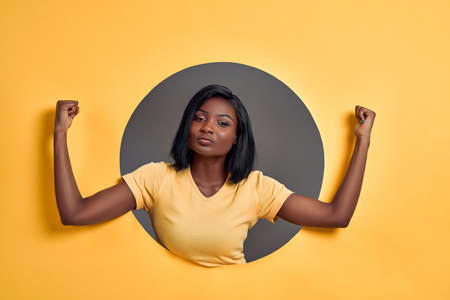 Woman raises hands and shows muscles, demonstrates her strength, wears yellow t-shirt, says: I am winner or champion. People, triumph concept. Feminism.