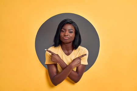 Young woman standing wearing casual t-shirt in a round circle hole in orange background pointing to both sides with fingers, different direction disagree. Copy space.