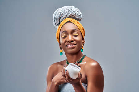 Beautiful young African American woman applying cream on skin on gray background. Copy space Foto de archivo