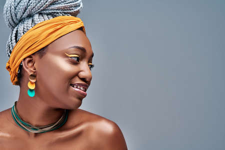 Side view of young fashion african woman wearing yellow headscarf on gray background. Copy space Banque d'images