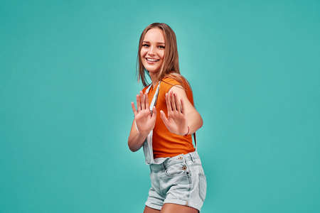 Portrait of a beautiful girl showing stop sign with palms isolated on a blue background. Copy space