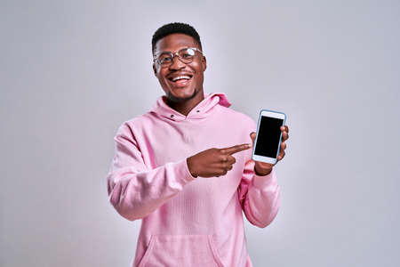 Cheerful afro american man dressed in a pink hoodie and glasses holds a phone and shows on his screen. The concept of gadgets and advertisements.