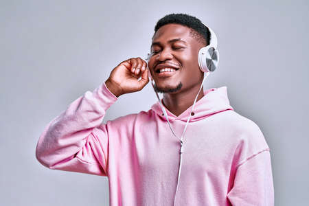 I enjoy the music! Young handsome african american man holds stylish silver earphones and smiles while looking at free space on a gray wall.