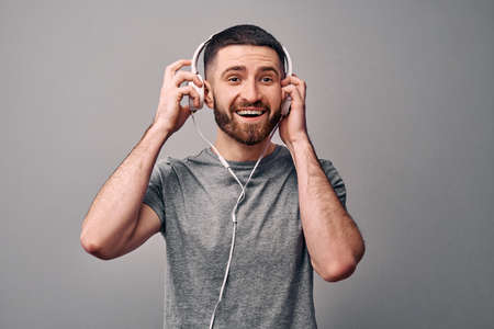 Music is my life. Young handsome man listens to music in white headphones, smiles and enjoys. Funny live emotions.