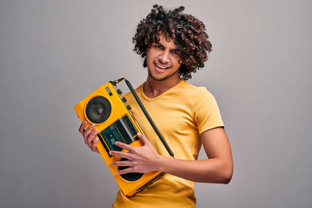 Young arabian handsome man enjoying music from bright retro stereo tape player on isolated gray background. Nostalgie, 90s concept. 版權商用圖片