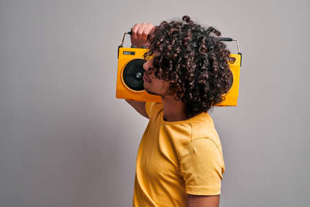 Young indian student enjoying sounds of retro music from vintage stereo player standing against gray background Banque d'images