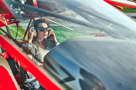 Woman pilot sitting in cabin of small aircraft. Side view. Shot throught the glass