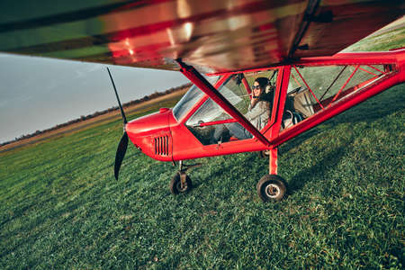 Small light airplane with woman pilot ready to flight on the airport field. Copyspace