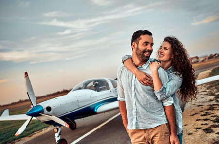 Happy young couple laughing and having fun on runway near private aircraft. Standard-Bild