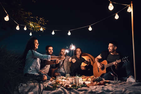 Group of friends camping together with sparklers and enjoy picnic party in a countryside.Travel vacation and adventure activity time concept. Low angle