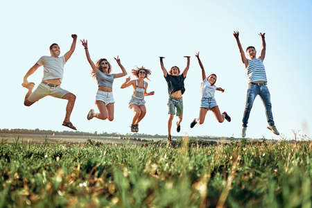 Group of friends jumping in the park on sky background. Summer, holidays, vacation, happy people concept. Bottom view