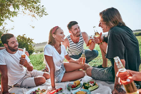 Group of teenagers having a picnic on the park. Young friends sitting together with beers in park. Young friends enjoying picnic Stock fotó