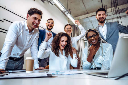 The concept of success. A group of young business people learned good news their project was approved in the work. Company development and joy.