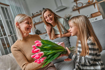 Gift for grandmother. Mother and daughter give a bouquet of pink tulips. The concept of family, generation, respect for elders and love. Mother's Day, Women's Day.