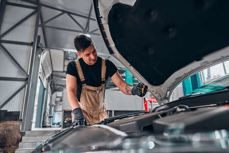 Mechanic checking oil level in a car workshop. Selective focus. Low angle view. Stockfoto