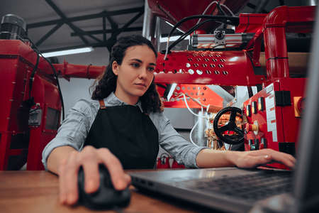 Woman using a laptop while operating a modern coffee roaster. Modern roaster on background.