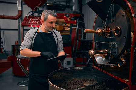 Portrait of cheerful bearded worker using tablet while locating near coffee roaster with spinning cooler professional machine. Industry concept. Stock Photo