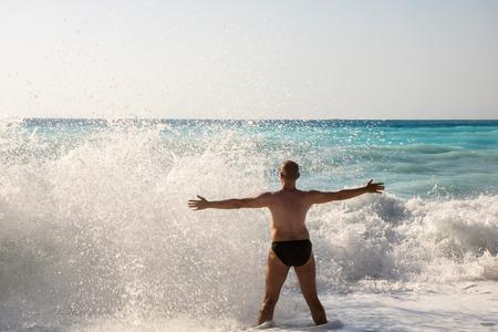 Man chasing the waves on Myrtos beach, island Kefalonia, Greece