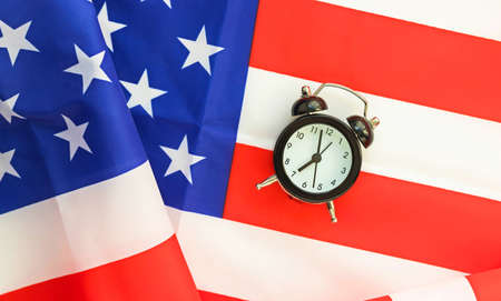 Alarm clock on American flag. President elections, Memorial Day, 4th of July or Labor Day concept. Patriotism and independence. Time to vote.