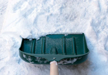 Green plastic shovel for snow removal. Winter season. Cold weather. Cleaning snow after snowstorm. Can be used for online article or report. Stockfoto