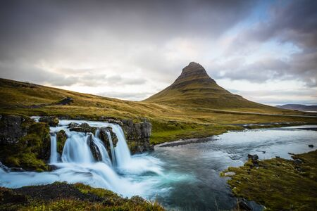 The picturesque sunset over landscapes and waterfalls. Kirkjufell mountain, Iceland Standard-Bild - 145438409
