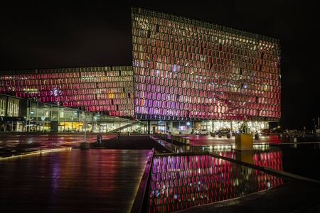Harpa concert hall in Iceland at night lights up in multiple colors, reflecting on a pool at the front of the building Standard-Bild