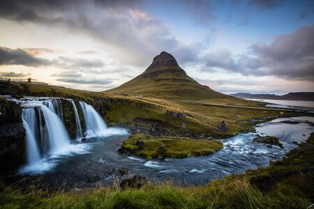 The picturesque sunset over landscapes and waterfalls. Kirkjufell mountain, Iceland Standard-Bild - 145438490