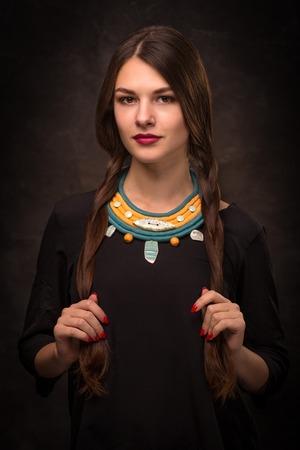 Beautiful female brunette model in handmade accessories fashion jewelry necklace. Fashion photo. Stock Photo