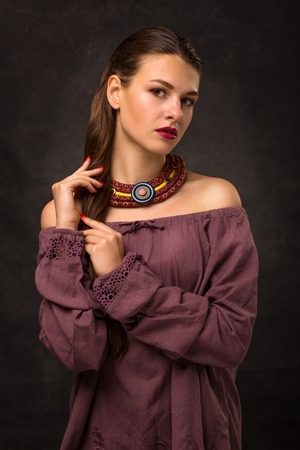Beautiful female brunette model in handmade accessories fashion jewelry necklace. Fashion photo. Фото со стока