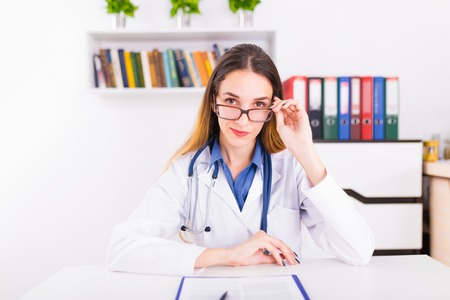 Young female doctor in uniform in doctors ofice writting a document