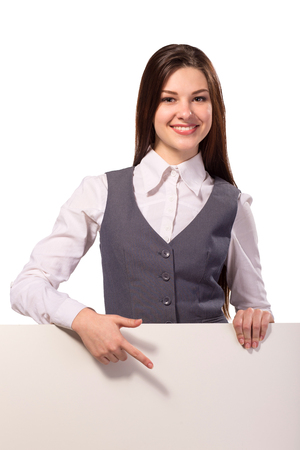 Young smiling woman pointing on blank board isolated on white