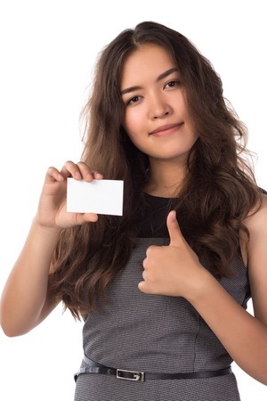 Young smiling asian woman holding a blank card, shows thumbs up gesture isolated on white Stockfoto