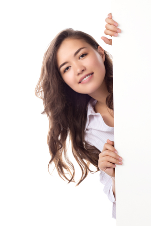 Young smiling asian woman showing blank white placard. Isolated on white background.