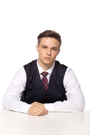 Casual young businessman working in office, sitting at desk, thinking about something, looking at camera